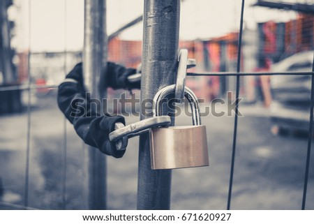 chain and padlock on gate at construction site - lock on closed fence