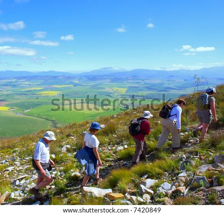 Chain group of hikers in misty majestic mountains. Shot in Swartberg Mountains, Caledon, Western Cape, South Africa.