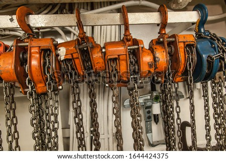 Chain hoists for lifting weights in a workshop close-up.