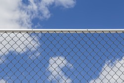 Chain Link Fence against a Cloudy Blue Sky