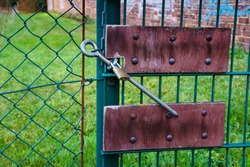 Chain link fence. Rusty riveted plates and padlock. Green grass behind the fence.