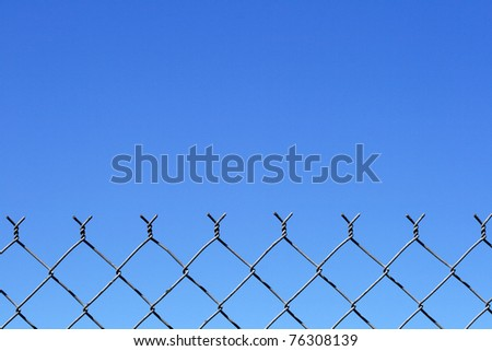 chain link fence top with blue sky background and copy space