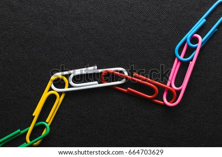 Chain made of paper clips on black background,teamwork and success concept.