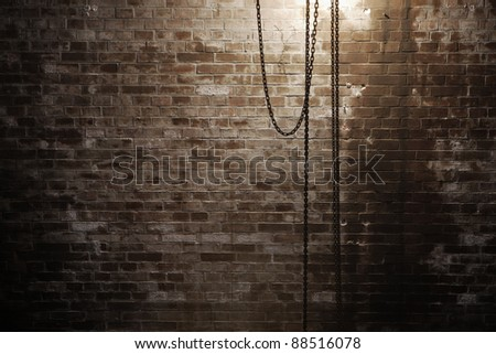 Chain of crane in front of the brick wall.
