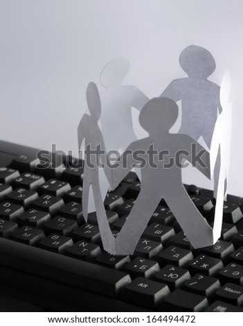 Chain of paper people on the keyboard isolated