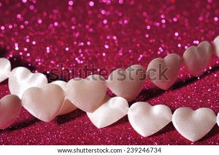 chain of white textilehearts on pink sparkle background