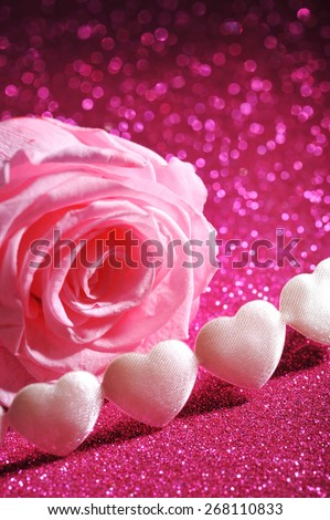 chain of white textilehearts with pink rose on pink sparkle background