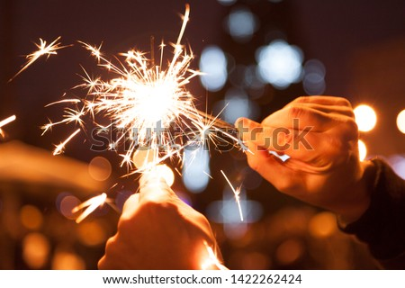 Chain Reaction Bengal Lights. Bengal lights in male hands set fire to each other on Christmas tree lights background #1422262424