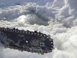 Chain saw blade in the snow infront of a ice hole with cold water