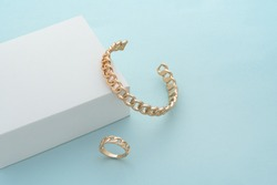 Chain shape cuff bracelet and ring on white box on blue background with copy space