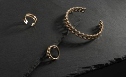 Chain shape gold bracelet and rings on black stone plates