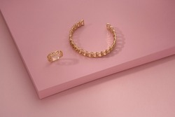 Chain shape golden bracelet and ring on pink background