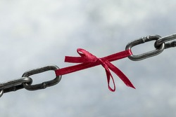 Chain tied by red ribbon, weak chain link concept on grunge background