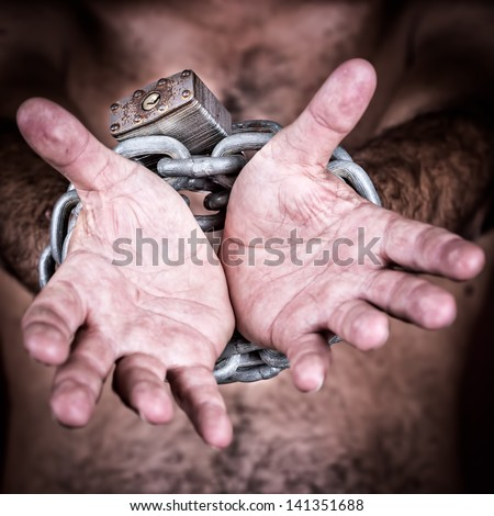Chained hands gesturing to symbolize the need for freedom  (in a dark background)