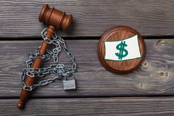 Chained judge hammer and dollar sign.
