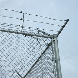 Chainlink fence corner with barbed wire top barrier