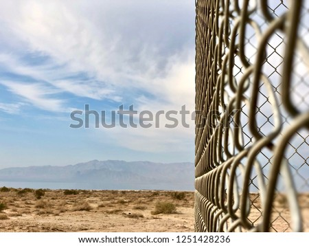chainlink fence taken at an angle in the desert with mountains in the background