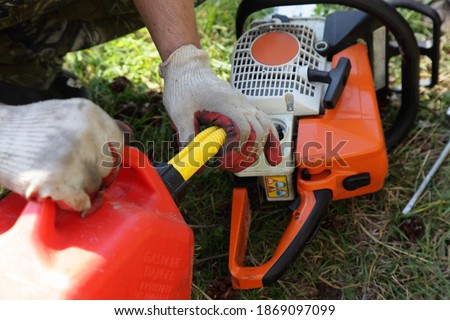 Chainsaw fueling process, filling motorsaw from hand with red can with gasoline fiel mix close up, wood sawing preparation at Sunny summer day on green grass background Foto stock ©
