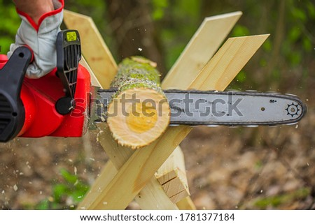 Chainsaw in action cutting wood. Man cutting tree trunk into logs with saw on sawhorse. Chainsaw. Close up of woodcutter sawing, saw in motion, sawdust fly to sides. Wood work, cutting tools, timber