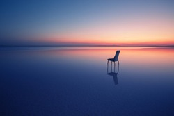 Chair among smooth water of lake at sunset. The concept of solitude and unity with nature. A chair stands in the water of the Salt Lake Ace. Anatolia, Turkey