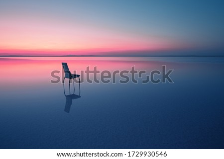 Chair among smooth water of lake at the sunset. The concept of solitude and unity with nature. A chair stands in the water of the Salt Lake Ace. Anatolia, Turkey Stock photo ©