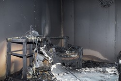 chair and furniture in room after burned by fire in burn scene of arson investigation course