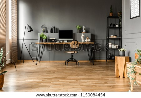 Chair at wooden table with computer monitor and plants in grey spacious home office interior