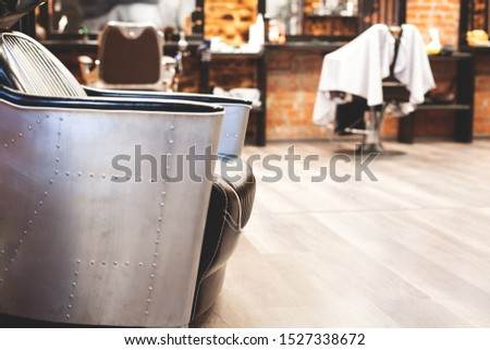 Chair for washing your hair in a barbershop. Barbershop interior. Brutal place. Leather armchair with metal upholstery. Selective focus