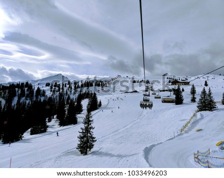 Chair lift/ ski lift in a ski resort in the Alps in Austria, Europe. Skiers and snowboarders on the slope. Amazing winter landscape with snowy mountain peaks. Skiers taking the chair lift to the top #1033496203