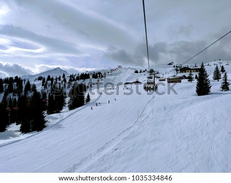 Chair lift/ ski lift in a ski resort in the Alps in Austria, Europe. Skiers and snowboarders on the slope. Amazing winter landscape with snowy mountain peaks. Skiers taking the chair lift to the top #1035334846