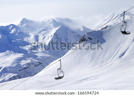 Chair lifts and off-piste slope in haze. Caucasus Mountains, Georgia, ski resort Gudauri.