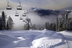 Chair ski lift in Krasnaya Polyana, Sochi, Russia on Chugush mountain peak background in Caucasus Mountains at snowy winter. Ski tracks of Gazprom ski resort on sunny day. Scenic landscape