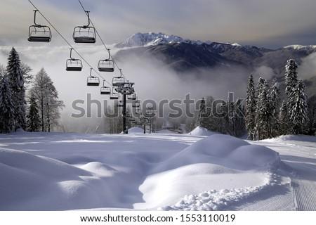 Chair ski lift in Krasnaya Polyana, Sochi, Russia on Chugush mountain peak background in Caucasus Mountains at snowy winter. Ski tracks of Gazprom ski resort on sunny day. Scenic landscape