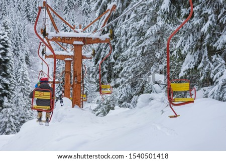 Chair ski lift next to slope for skis and snowboards. Skiers are sitting at old fashioned chair ski lift. Ski area in snowy high mountain. Sports and recreation concept. Selective focus. #1540501418