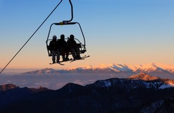 Chair ski lift with skiers over blue sky in the evening