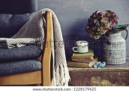Chair with blanket, books and hydrangea flowers in grunge zinc vase can on vintage wooden cabinet. Hygge home interior concept #1228179625