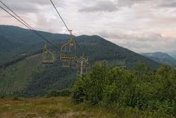 Chairlift ski lift in Carpathian mountains leading from mountain station. Transporting hikers in summer season.  Zakarpattya, Ukraine.