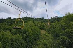 Chairlift ski lift in Carpathian mountains leading to mountain station. Transporting hikers in summer season.  Zakarpattya, Ukraine.