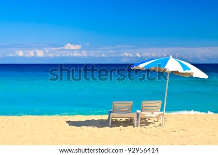 Chairs and parasol on the beautiful cuban beach of Varadero with a clear blue sky useful to add text