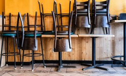 Chairs and Stools Stacked on Tables in an Empty Closed Restaurant during Covid-19 Pandemic