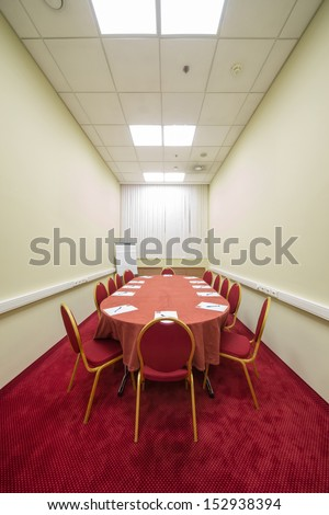 Chairs and table in empty conference room with a red carpet on the floor