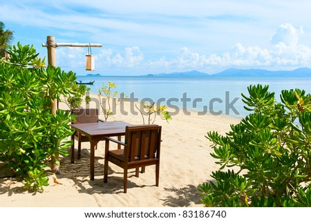 Chairs and table on beach near the sea - stock photo