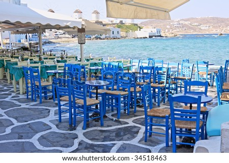 "Chairs and tables of restaurants in the area of ""Little Venice"" in Mykonos island, Greece"