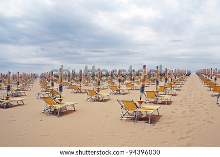 chairs, beach chairs and umbrellas closed in a line along the sandy shore in a day without sunshine