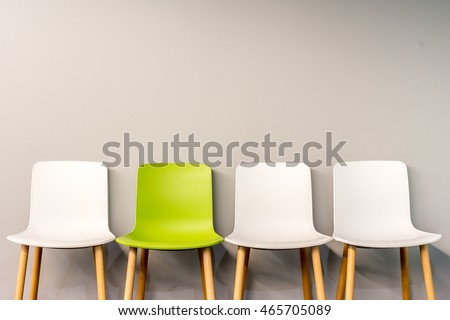Chairs in modern design arranged in front of the gradient grey wall for interior or graphic backgrounds. The chair in different color can be used as a metaphor to represent the hiring position.