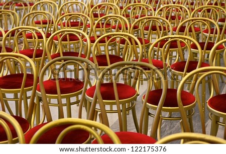 Chairs in the hall. Hall interior. Many red chairs with golden frames in big hall, not clear, background, pattern.