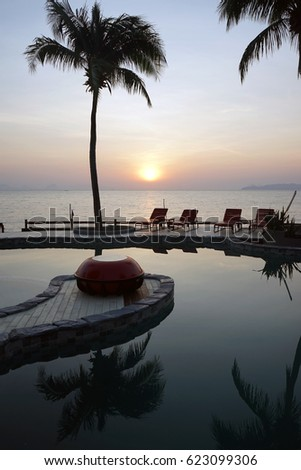 Chairs near pool with water and sea with sunset in Thailand #623099306