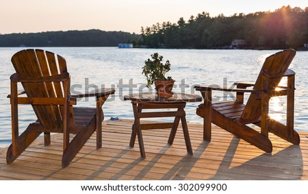 Chairs on a deck overlooking a lake at sunset