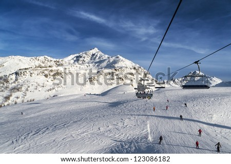 chairs on ski lift above a slope in high mountain