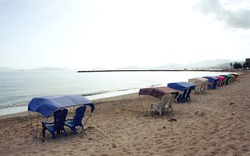 Chairs underneath color coordinated awnings with view to beach. Lecheria city, Venezuela.